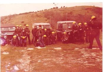 Foto vecchia di uomini in tuta verde e casco giallo