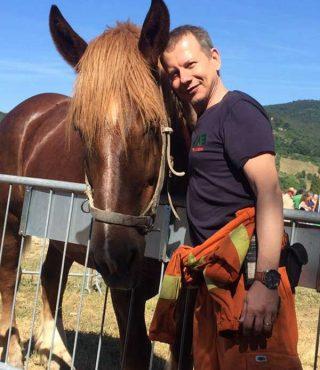 contattaci Uomo vestito con tuta arancione protezione civile e maglietta blu accanto a cavallo