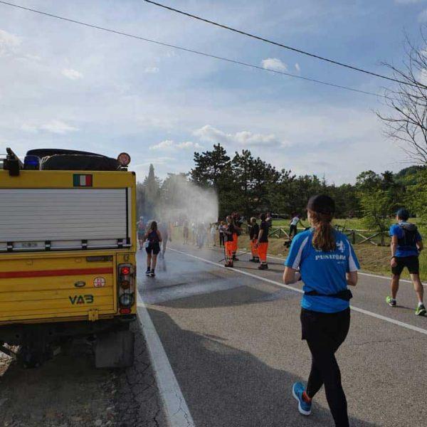 Auto gialla e Uomini in tuta arancione e blu Protezione Civile che bagnano corridori