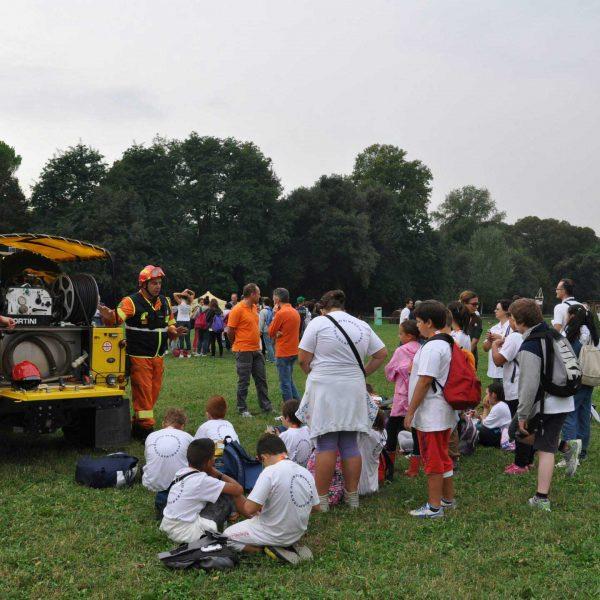 Due uomini in tuta arancione Protezione Civile vicini ad auto gialla insieme a bambini