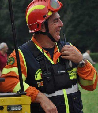 contattaci Uomo vestito con tuta arancione Persona con tuta arancione appoggiata su auto gialla Protezione Civile, casco rosso e gilet nero