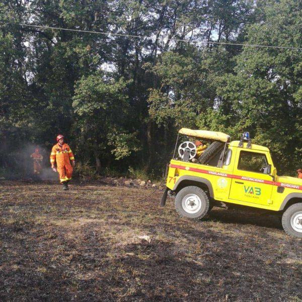 Auto gialla Protezione Civile su prato bruciato