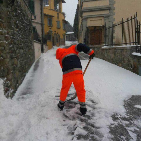 Persona della Protezione Civile in tuta arancione che spala neve su strada in salita tra le case