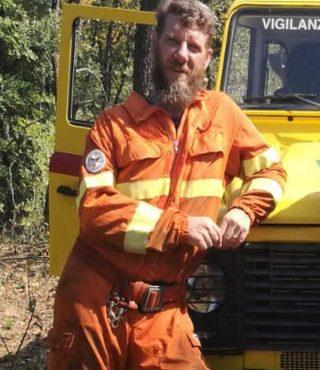 contattaci Persona con tuta arancione appoggiata su auto gialla Protezione Civile
