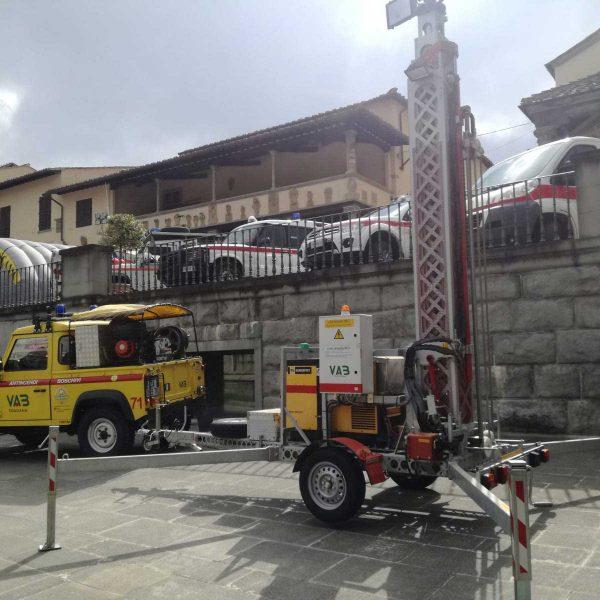 Auto gialla Protezione Civile e torre faro vicino a muretto di un parcheggio