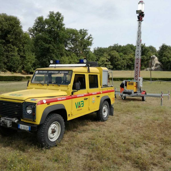 Auto gialla Protezione Civile e torre faro su di un prato circondato da alberi